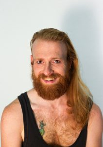 Een lachende man met lang roodblond haar over de schouder. Hij draagt een zwart hemd en heeft een tattoeage van een groene eend op zijn linkerborst.